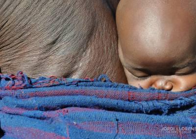 Niño surma durmiendo en la espalda de su abuela, Valle del rio Omo, Etiopía